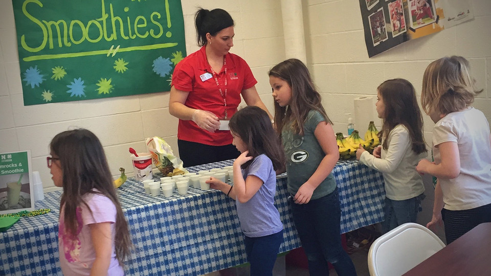 Nebraska Extension Educator Kayla Colgrove shares smoothie samples with Tri County Public Schools students during a recent farmers market at the school.