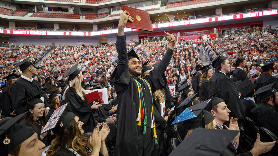 Nadir Al Kharusi shows off his diploma to family and friends during the undergraduate commencement ceremony Dec. 16 at Pinnacle Bank Arena. Al Kharusi stood after Chancellor Ronnie Green asked first-generation college graduates to stand and be recognized. He earned a Bachelor of Arts.