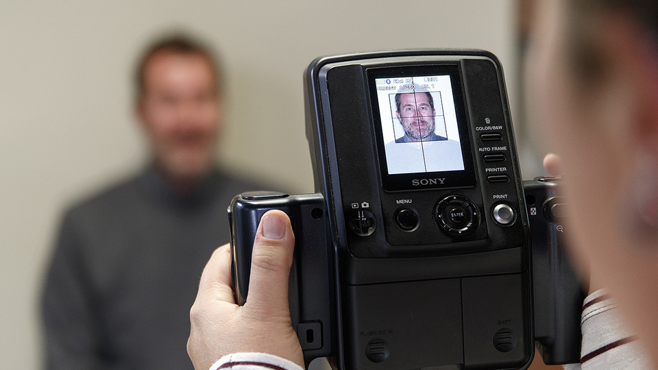 Scott Hurst has his picture taken Jan. 23 in the University of Nebraska-Lincoln Passport Office, 1700 Y St. The office is open 8 a.m. to 5 p.m. Monday through Friday.