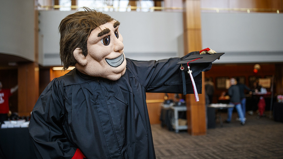 Herbie Husker gets fitted with a commencement gown during Nebraska Gradfest in late November at the Wick Alumni Center. The university's December commencement exercises are Dec. 14 and 15 at Pinnacle Bank Arena.