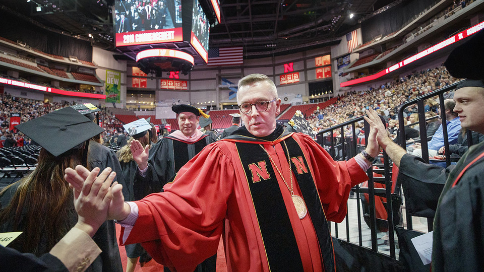 Chancellor Ronnie Green and Kevin Hanrahan, associate professor of voice and vocal pedagogy and Faculty Senate president, give high-fives to graduates as they walk onto the Pinnacle Bank Arena floor Dec. 15.