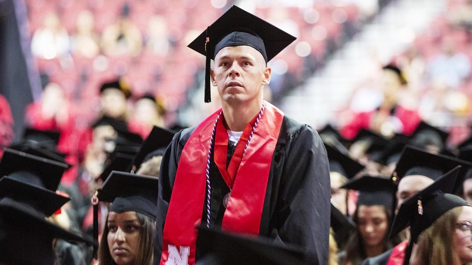 Eric Alan Bohnenkamp stands to be recognized during the summer commencement ceremony Aug. 17 at Pinnacle Bank Arena. He was commissioned a second lieutenant in the U.S. Marine Corps on Aug. 17.