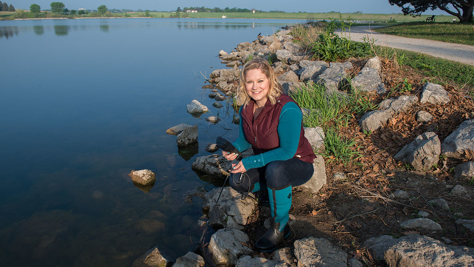 """Tiffany Messer, assistant professor of biological systems engineering at the University of Nebraska–Lincoln, tests water in Lincoln's Holmes Lake in May 2018. Messer's research is included in the new traveling exhibition """"H2O Today,"""" which opens Jan. 26 at the University of Nebraska State Museum at Morrill Hall."""