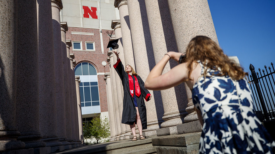 Rose Wehrman of Kenesaw is photographed by Sarah Schilling of Omaha. The two graduates borrowed a cap and gown from a friend who graduated last year to take photos of each other on campus April 30. Wehrman earned a Bachelor of Arts with distinction, and Schilling earned a Bachelor of Science in Business Administration with high distinction.