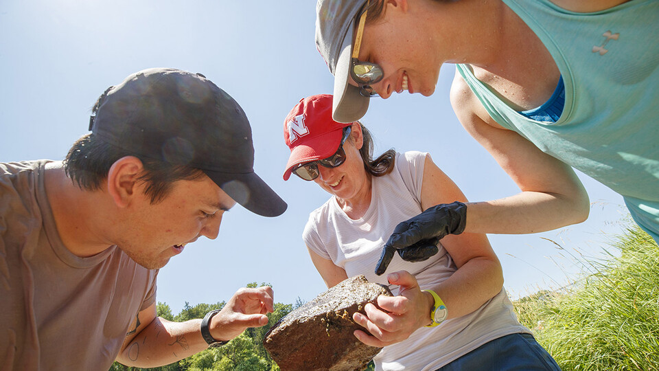 Jessica Corman (center), assistant professor in the School of Natural Resources, discusses a rock teaming with aquatic life with students Matthew Chen and Kayla Vondracek during a UCARE project on the Niobrara River in July 2019.
