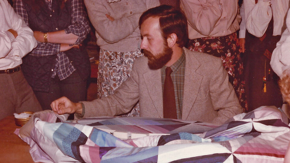 Michael James demonstrates his hand-quilting method for workshop participants at Strawberry Fayre, a quilt shop in Stockbridge, England, in 1980. The shop's owners, Jenny and Alec Hutchison, were responsible for bringing James to England for the first time in 1980. Through the '80s and '90s, he lectured and taught workshops there and throughout Europe annually, networking widely with fellow quilt artists.