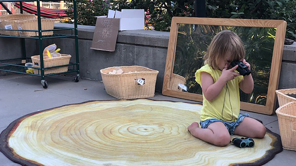 A child plays with binoculars at the Ruth Staples Child Development Laboratory, where outdoor learning is the norm.