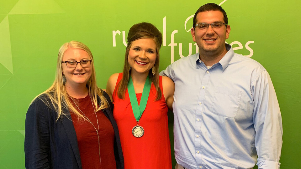 Fellows program leaders Amber Ross (left) and Andrew Ambriz (right) stand with one of their four student fellows, Megan Coan (middle), during a celebration at the end of the 2019 program.