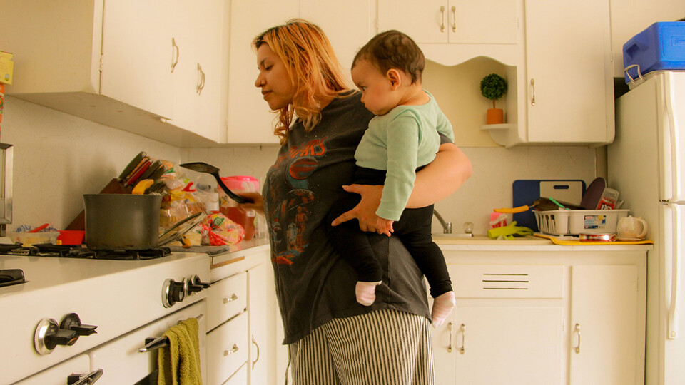 """In this photo from Luci Moran's essay """"The Nature of Motherhood,"""" Sam Vargas prepares lunch for her children while carrying her daughter. """"After you have your baby, the hospital will give you a doctor that will tell you, 'You can call me if you need anything at all, here's my number,' and that's pretty much all you get,"""" Vargas said. """"I remember with my second child, for a moment I felt like I needed help, but I never reached out. It felt like a phone call just wasn't enough."""""""