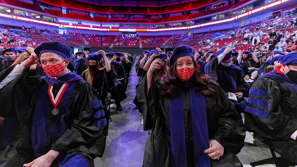 Samuel Baue (left) and Anna Bauerie move the tassels on their tams at the conclusion of the College of Law graduation ceremony May 7 at Pinnacle Bank Arena.