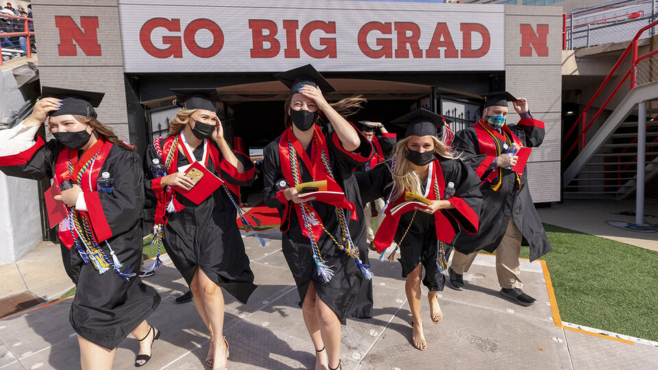 Graduates hang on to their mortar boards and stoles as they walk onto the field at Memorial Stadium for the morning undergraduate ceremony May 8.