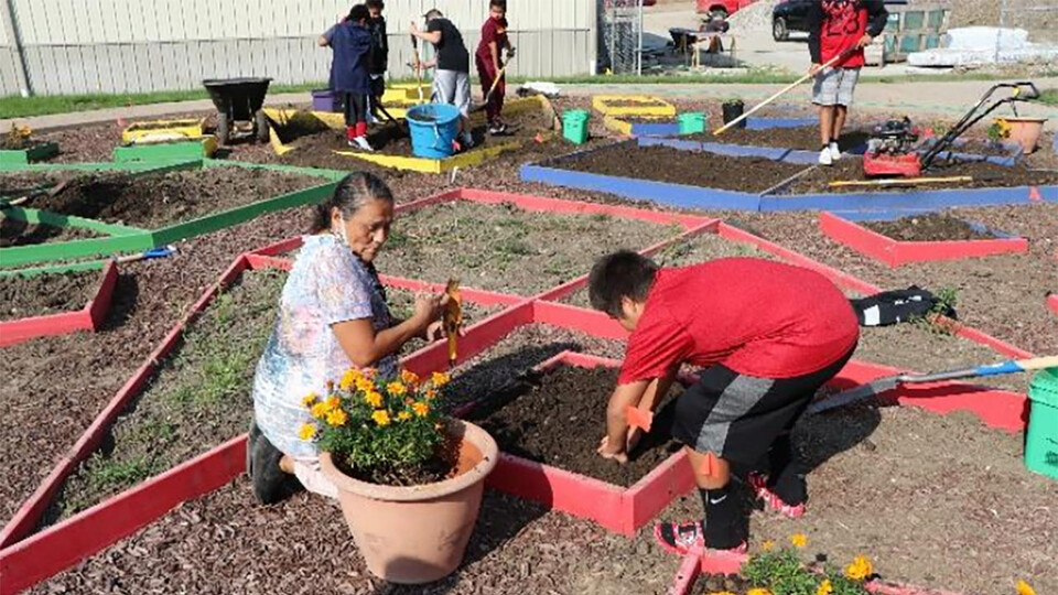 Elder and teacher Delberta Frazier sows traditional plants with students in the Umonhon Nation Public School garden.