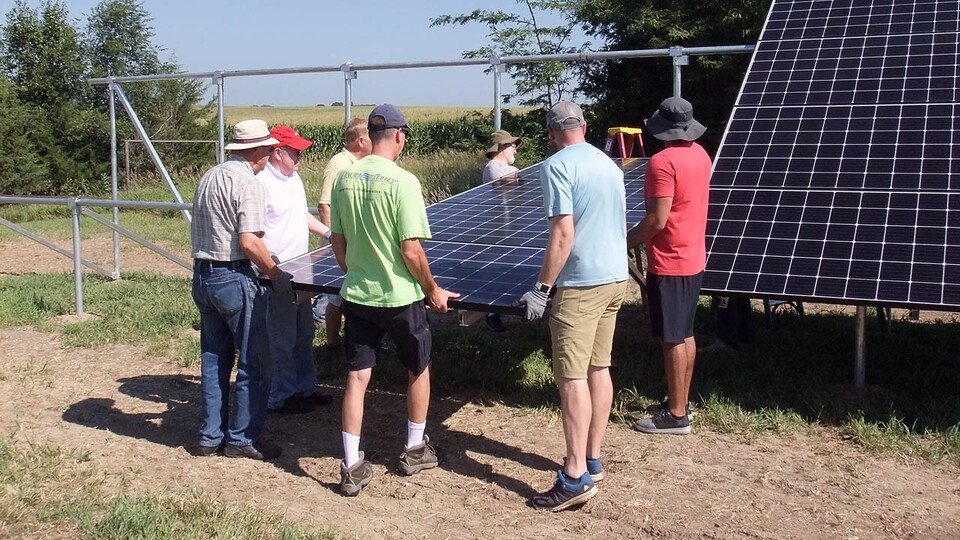 Workshop participants help assemble a solar photovoltaic array at a hands-on workshop during summer 2018.