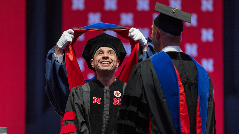 Ali Jamal Mazaltarim watches his doctoral hood being placed over his head during the graduate and professional degree ceremony Aug. 13 at Pinnacle Bank Arena.
