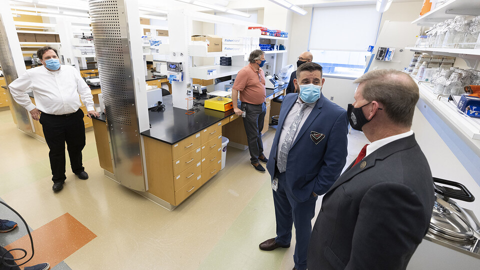 Joshua Santarpia (second from right), NSRI research director, answers a question from NU President Ted Carter (right) during a tour of the new Collaborative Biosecurity Laboratory on Sept. 27.