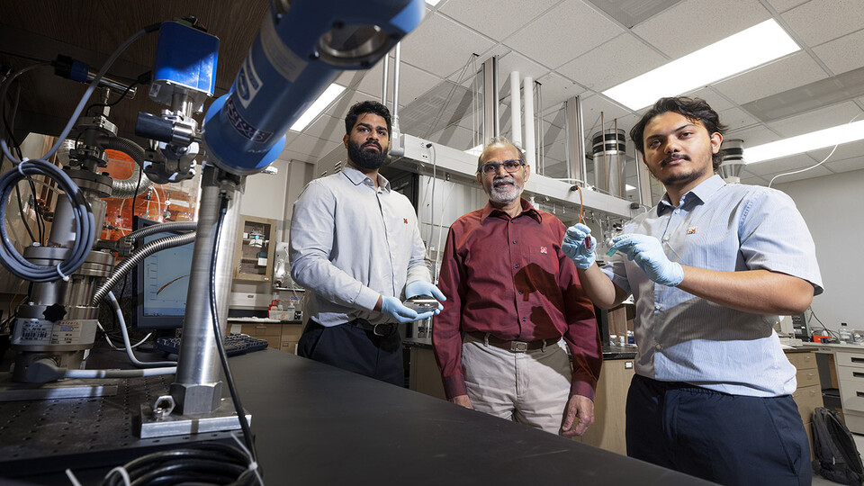 Abhijeet Prasad (left), a doctoral student in engineering; Ravi Saraf (center), Anderson Distinguished Professor of chemical and biomolecular engineering; and Aashish Subedi, a senior physics major, are photographed in Saraf's Othmer Hall lab. Prasad is holding small electronic chips used to study the nanoparticle necklace network devices. Subedi is holding a suspension of nanoparticle necklaces (blue container) made from individual particles (red container).