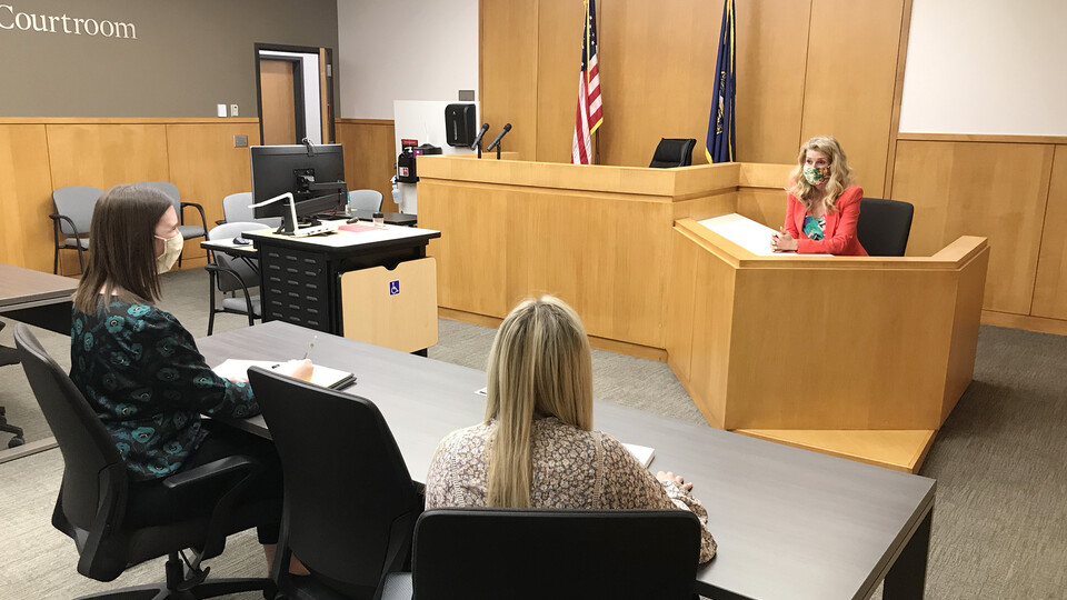Michelle Paxton, director of the Children's Justice Clinic, talks with two student attorneys in the Judge Donald R. and Janice C. Ross Courtroom in the College of Law. Clinic student attorneys practice with Paxton before going to court.