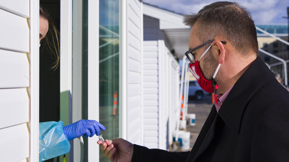Chancellor Ronnie Green hands his saliva vial to Kaitlin Cartwright at the collection site by East Memorial Stadium. Green was one of more than 4,000 Huskers who were tested on Jan. 19, the first day testing was offered to the entire campus community.