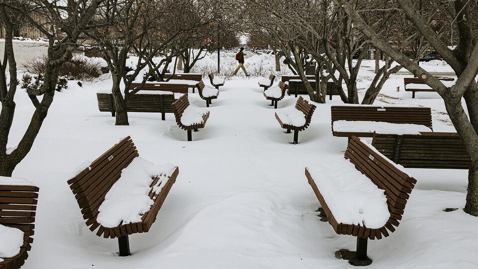 "A student walks by the snow-covered benches in the plaza north of the Lied Center for Performing Arts. After a record-setting snowfall delayed the start of the ""spring"" semester, the second week of February featured temperatures that have struggled to reach double digits."