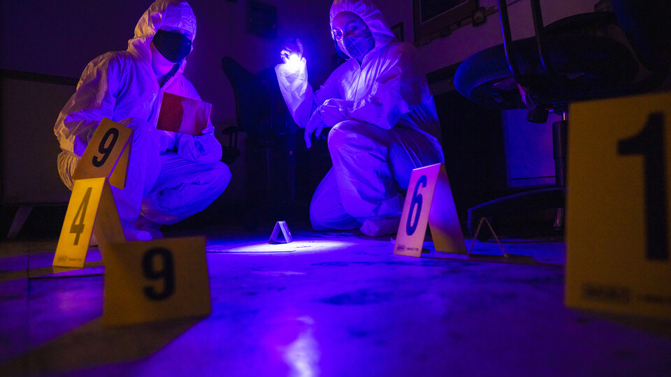 Symone Arends, a senior from Lincoln, shines an ultraviolet light onto the floor. The light will make body fluids and fibers  glow when viewed through the filter held by Alysa Ehlers, a senior from Woodbridge, Virginia. The two are working a mock crime scene in a basement room in Filley Hall.