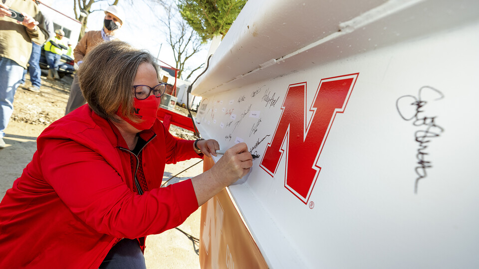 Sheri Jones, dean of the College of Education and Human Sciences, signs the final beam that was lifted into place during the April 9 topping out ceremony. An evergreen tree was also placed atop the beam, signifying the safe completion of the internal structure of the building.