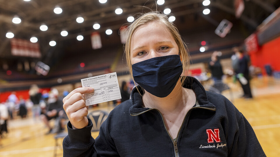 Nebraska's Whitney Steckel displays her vaccine card after getting her first inoculation during an on-campus clinic on April 20.
