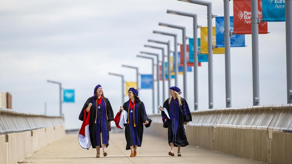 Nebraska Law graduates (from left) Claudia Brock, Sarah O'Neill and Rachel Lowe walk across the pedestrian bridge toward Pinnacle Bank Arena before commencement on May 7.