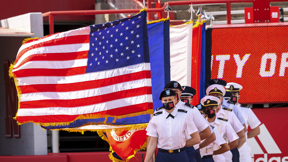 UNL's ROTC combined color guard stands at attention with flags in hand during commencement exercises in Memorial Stadium on May 8.