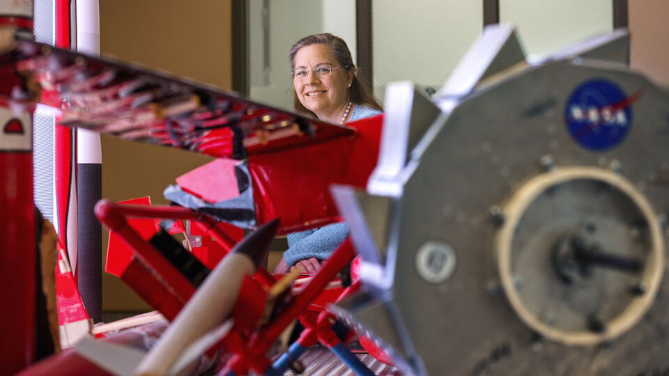 Karen Stelling is a professor of practice in mechanical and materials engineering. She is the adviser of the Aerospace Club, which is working on a satellite project with NASA, through a student grant project. She poses in the lobby of Othmer Hall with a display of Nebraska Engineering aerospace engineering projects.