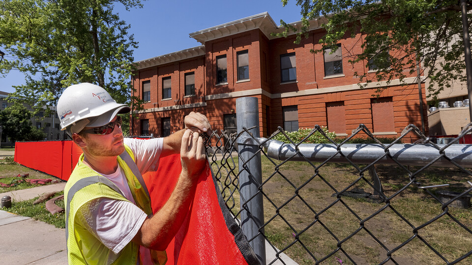 Miller Hall on East Campus is wrapped in construction fencing as the building will be demolished in the next few weeks.