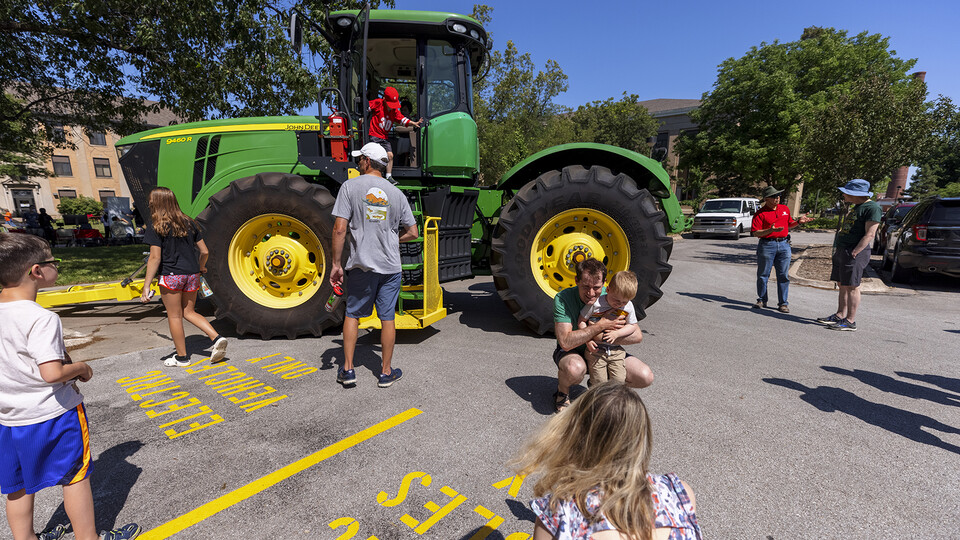 Children examine a John Deere tractor during East Campus Discovery Days on June 12.