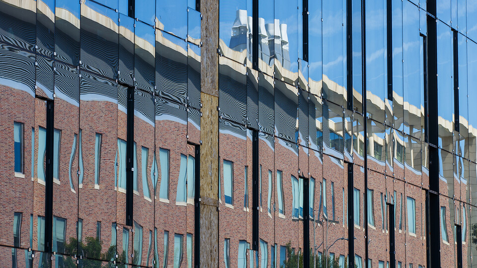 """Jorgensen Hall is reflected in the ongoing construction of the College of Engineering's first phase expansion. The project is replacing the """"Link,"""" which connected Nebraska Hall to the Walter Scott Engineering Center."""