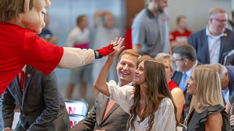 Herbie Husker gives a high five to Breanna Alberts, youngest daughter of Trev and Angie Alberts. Trev Alberts was announced as the university's next athletic director on July 14.