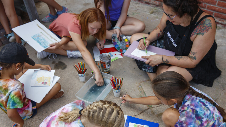 A counselor helps art students