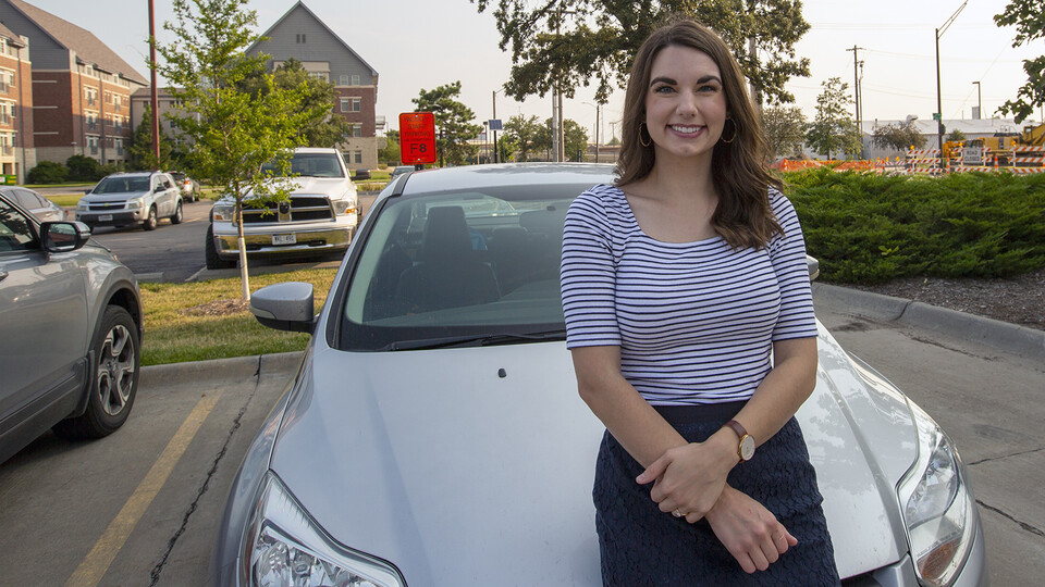 Nebraska's Bonnie Martin rests on her car after a quick commute on July 21. Martin  —who won free reserved parking for a year —was the first university employee to earn a prize through the voluntary vaccine registry giveaway.