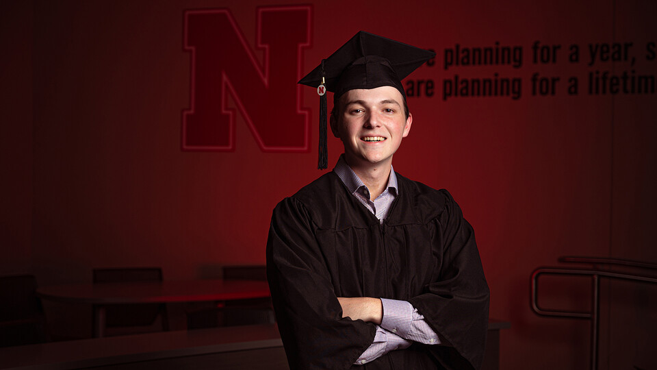 Business student Caleb Newburn stands, arms crossed, by a Hawks Hall wall decorated with the Nebraska N.