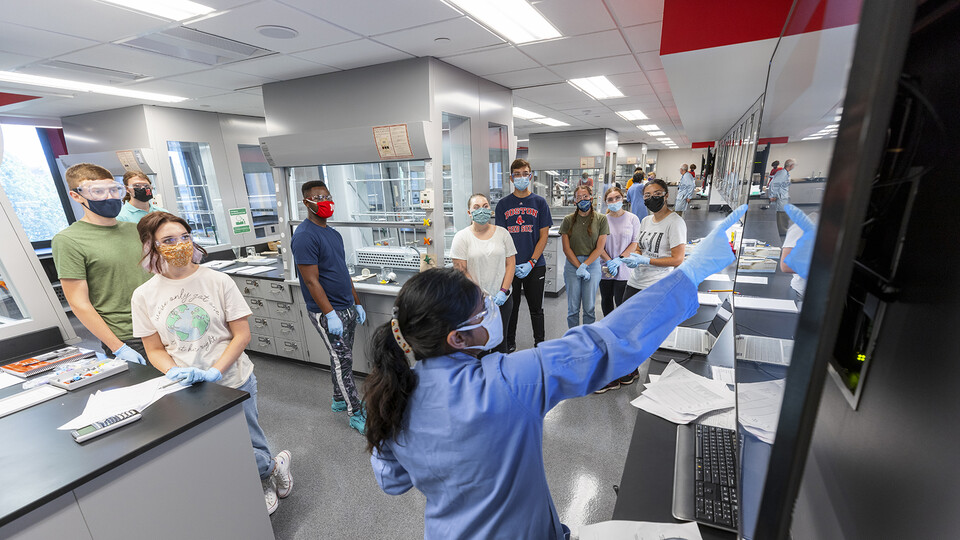 Students — all of whom are wearing masks — listen to instructions in the newly renovated organic chemistry labs in Hamilton Hall on Aug. 23, the first day of classes in the fall 2021 semester. Following an order from public health officials, the university community will start wearing masks when indoors on Aug. 25.