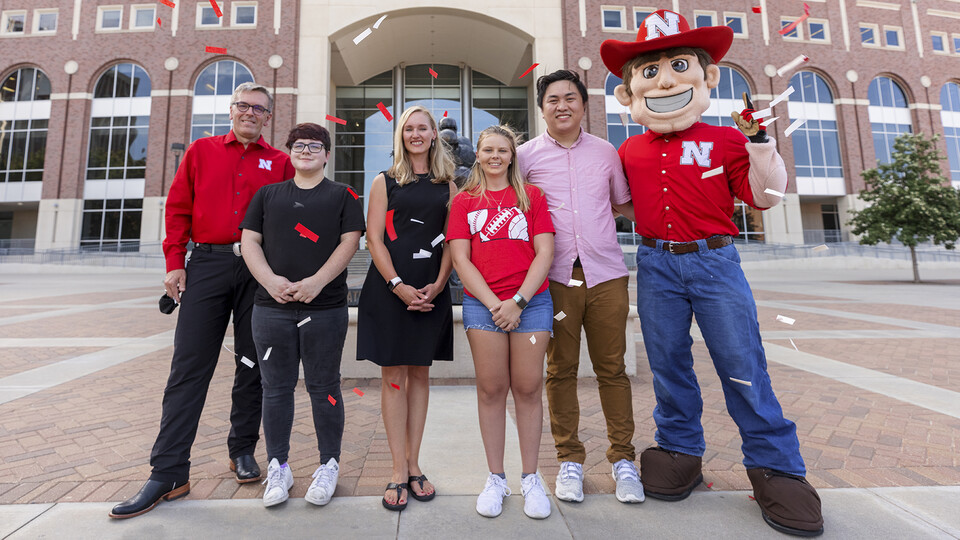 Voluntary COVID-19 Vaccine Registry grand prize winners stand with Chancellor Ronnie Green and Herbie Husker on the east side of Memorial Stadium.