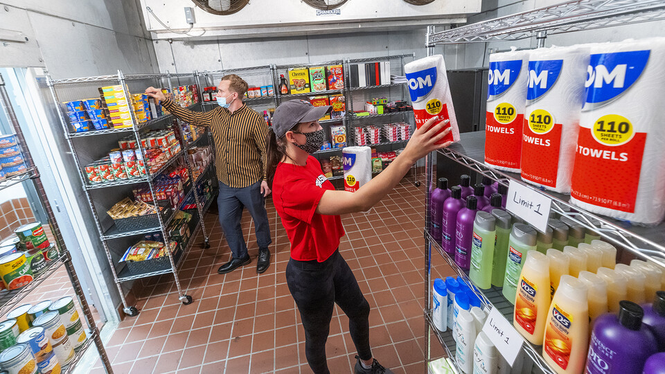 Morgan Berg (right), a senior in psychology from West Fargo, North Dakota, and Tim Anderson, a third-year law student from Huntington Beach, California, stock the shelves in the new East Campus Food Pantry. The pantry is in Filley Hall in the old Dairy Store walk-in freezer
