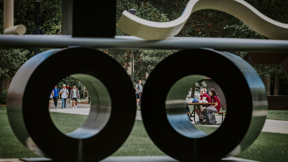 """Students framed in circles created by the campus sculpture """"Balanced/Unbalanced Wheels No. 2."""""""