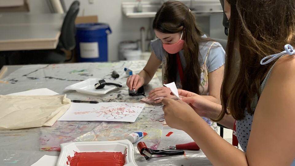Participants make stenciled fabric designs.