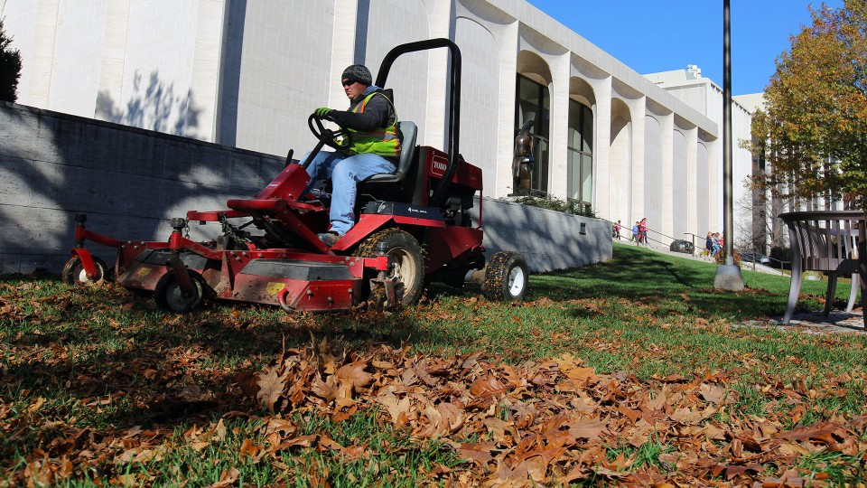 Tim Herron, a landscape assistant with landscape services, mulches leaves into the grass on the east side of Sheldon Museum of Art on Nov. 8. The university recently expanded it's sustainability practices by partnering with Big Red Worms on leaf recycling.