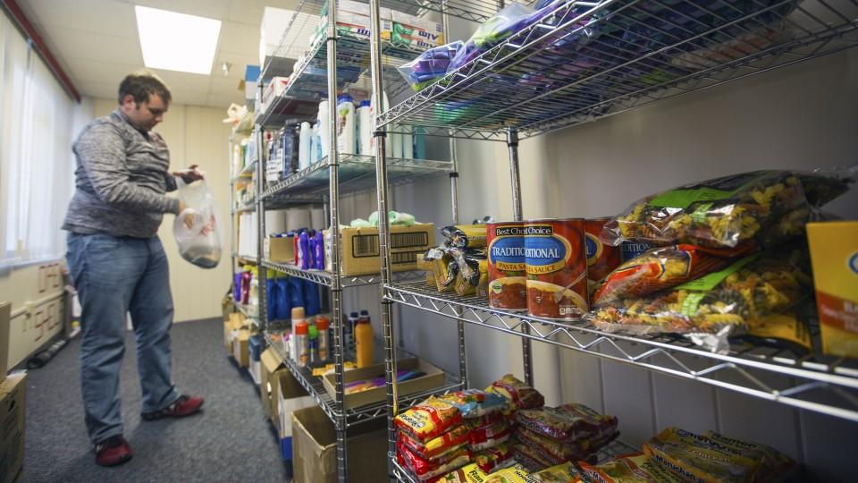 Cody McCain, a sophomore accounting and agribusiness major from Aurora, places donations on shelves in the university's current food pantry. McCain is the coordinator for the food pantry, which is located in the Lutheran Center. The university is opening an expanded food pantry in the Nebraska Union in January.