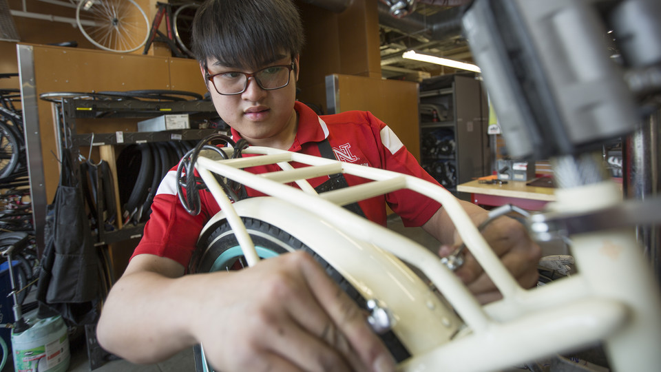 Kam Loong, a student employee, adjusts the rear brake on a Schwinn cruiser in the campus bike shop.