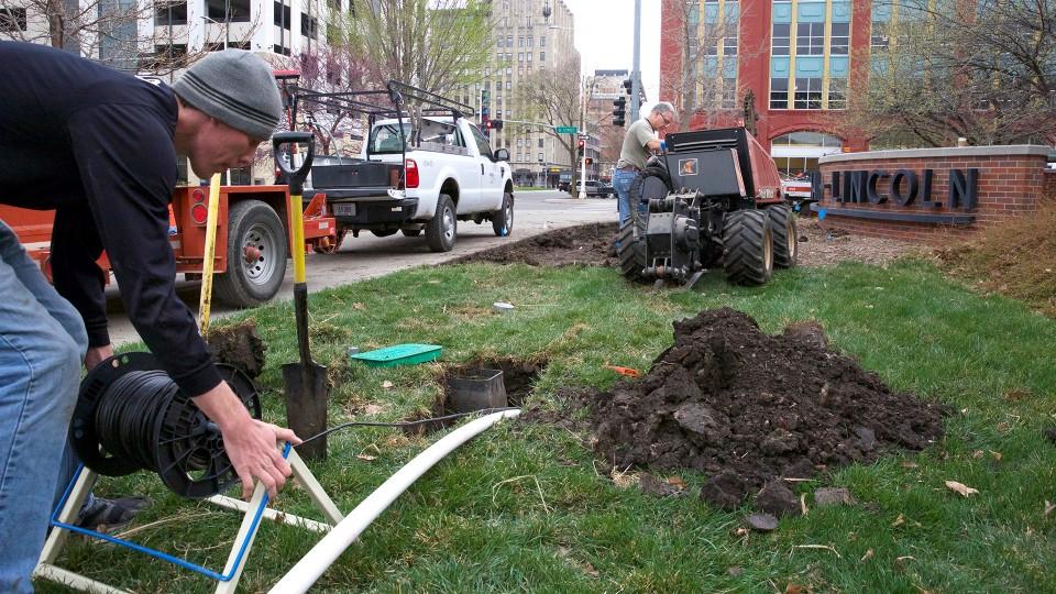 UNL landscape services employees Michael Tomjack (left) and Fred Thorne use a vibrating plow to install new irrigation pipe by the Van Brunt Visitors Center. UNL has started a campuswide upgrade of its irrigation system. When complete, it is projected to decrease campus water usage by at least 20 percent annually.