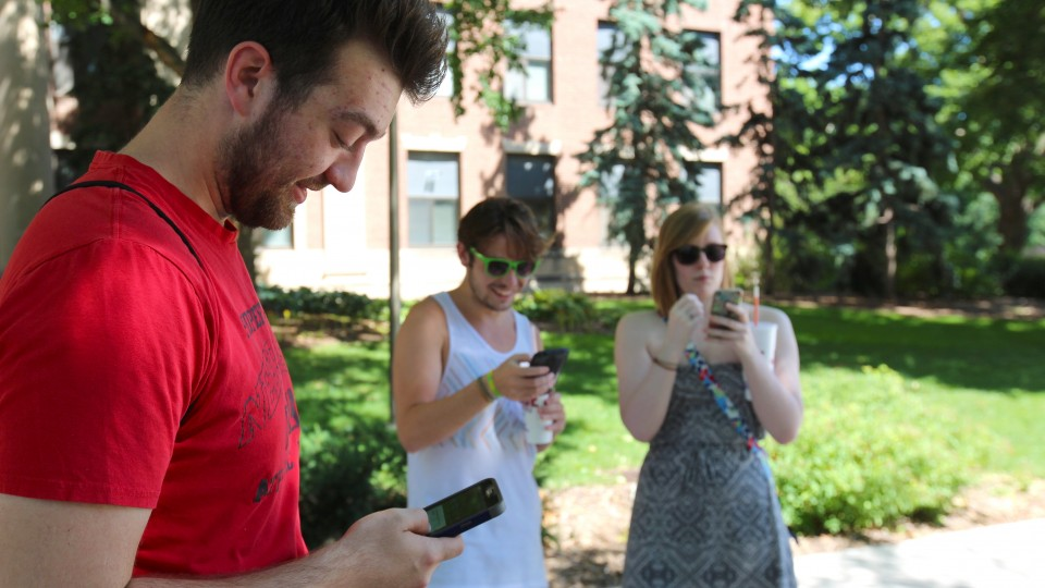 UNL students (from left) Thomas Kasper, John Sanders and Hanna Barnett battle in a Pokémon Go gym location near Sheldon Museum of Art on July 13. The game, which launched July 6, has quickly become one of the most popular apps available to smartphone users.