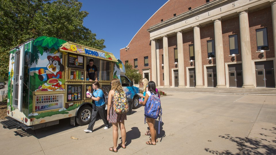 Students wait to order shaved ice from the Kona Ice truck outside the Coliseum on Sept. 20. The food truck is the first to take part in a new program offered by the Nebraska Unions.