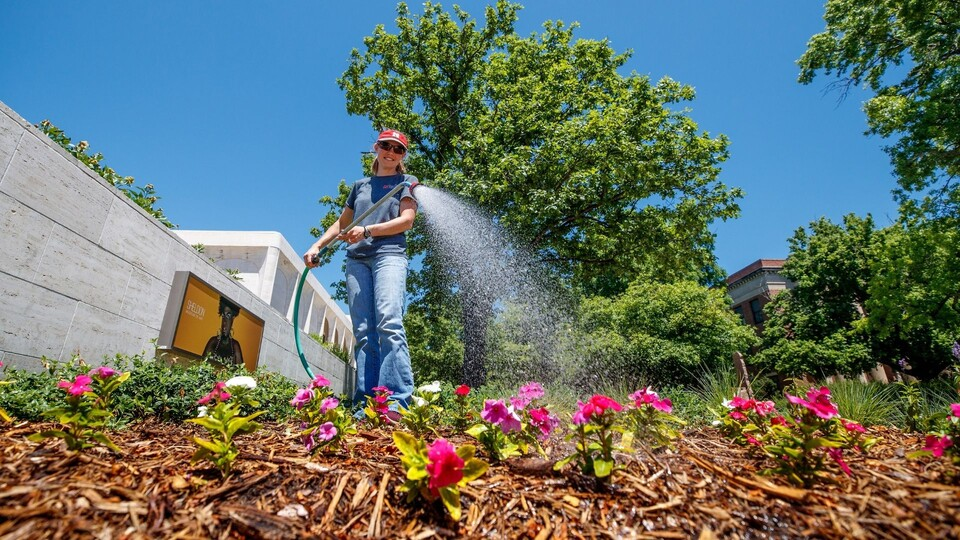 Student employee watering plants on campus