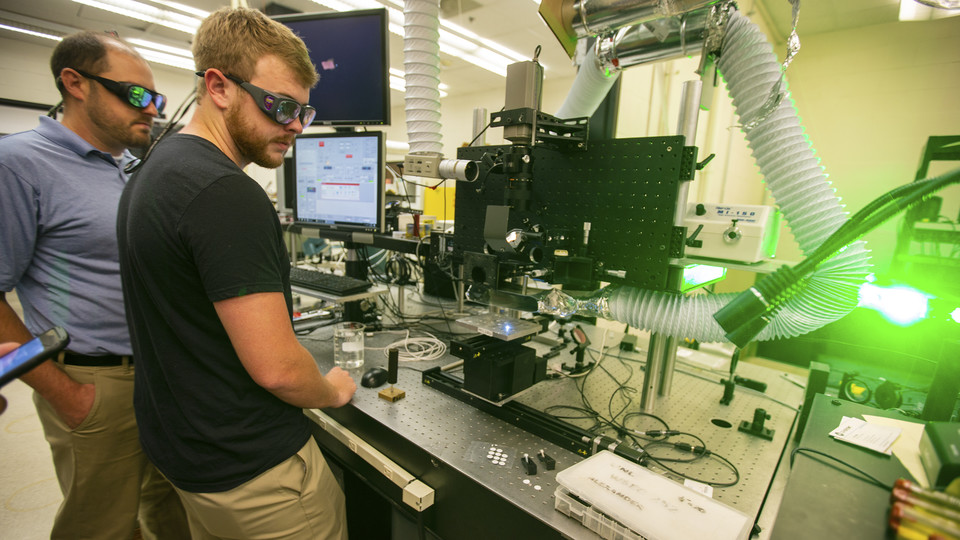 Craig Zuhlke, a research assistant professor, and Aaron Ediger, a graduate research assistant, watch as a laser modifies a small sample of metal. The research, led by Nebraska's Dennis Alexander, is modifying metal surfaces to mimic biological properties, including shark skin. The research is used primarily for defense and industrial purposes.