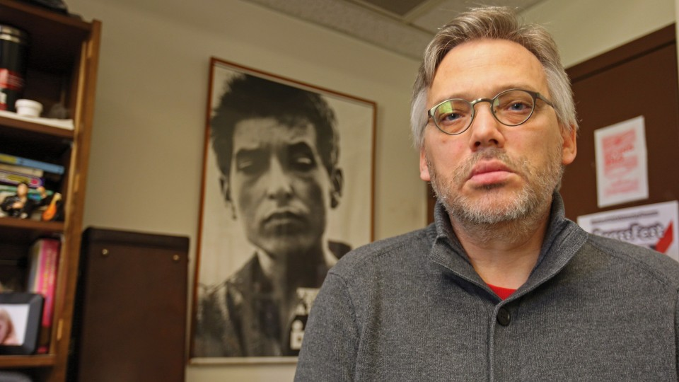 Scott Anderson, professor of music, mimics the look of Bob Dylan in the poster in the background. Anderson is teaching an honors course that focuses on Dylan, who earned the Nobel Prize for Literature on Oct. 13.